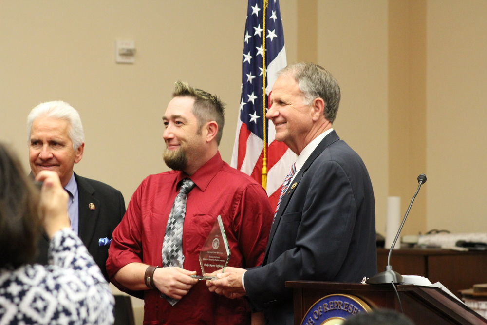 Bill Brady, center, accepts the award on behalf of TAT. Representative Costa, left, and Representative Poe presented the award.