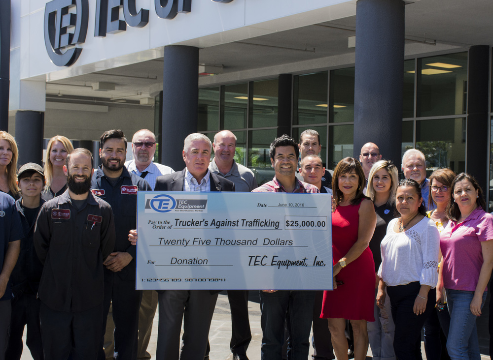Surrounded by a number of tec equipment employees, guido hajenius, (right center), received the check for tat tec equipment regional president victor salvino (left center).