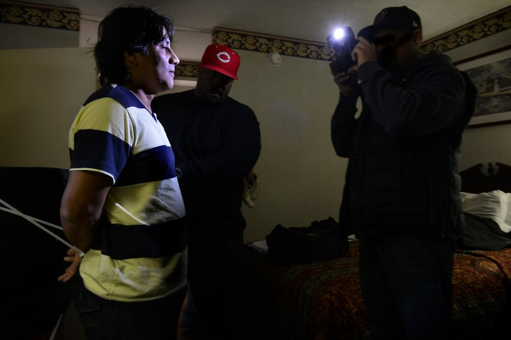 An officer takes a photo of a man in a motel room as Prince George's County police run a sting operation to nab prostitutes and johns in 2012 in College Park, Md. (Bill O'Leary/The Washington Post)