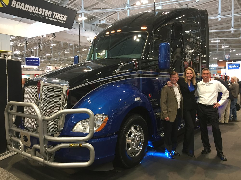 Don Blake from Inland Kenworth, Kendis Paris, executive director of TAT, and George Cravens of Utility Trailers pose in front of the custom Kenworth T680
