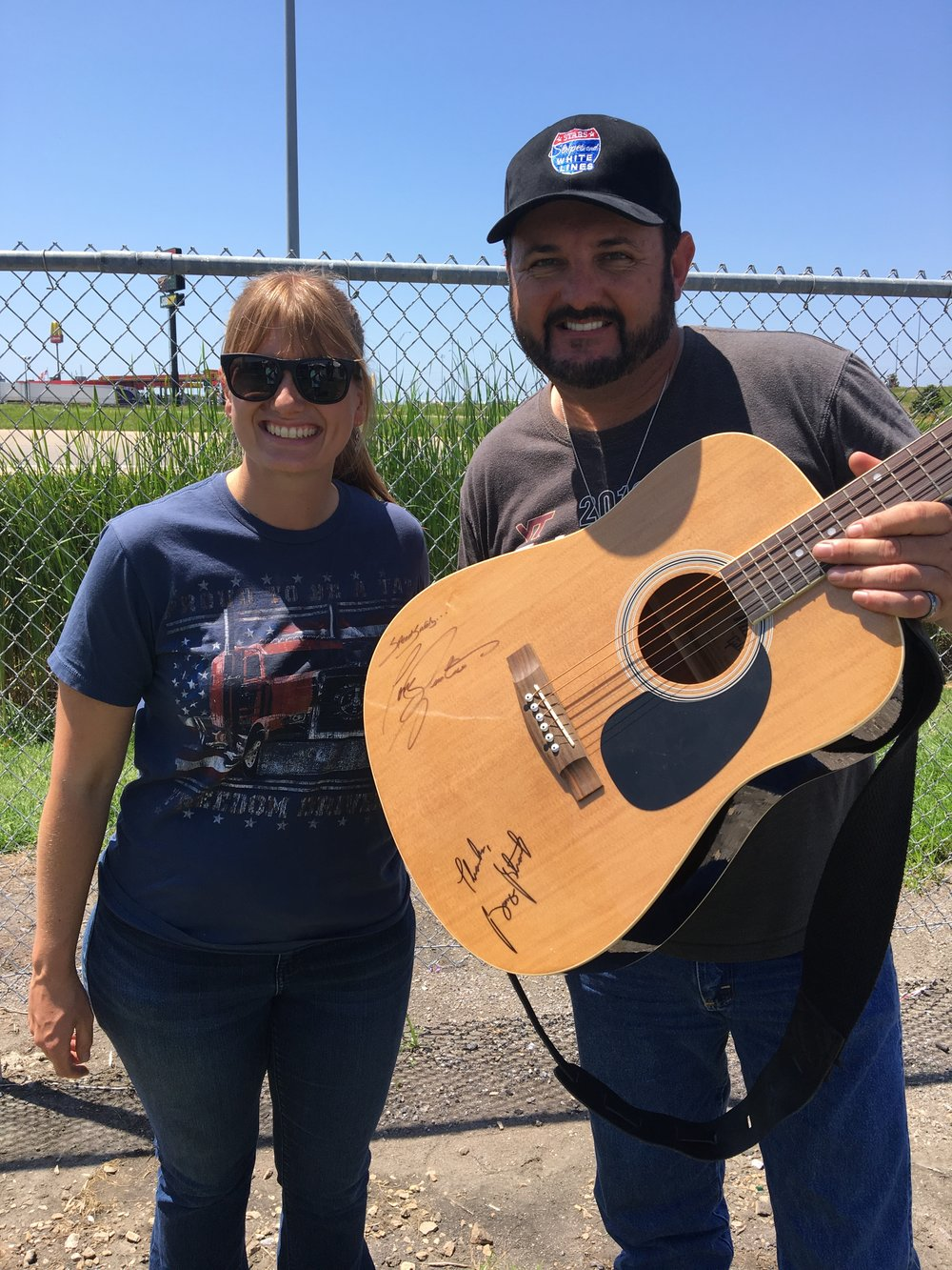 Helen Van Dam, TAT FDP director, checked out the guitar Tony Justice, country music star and truck driver, raffled off for TAT.