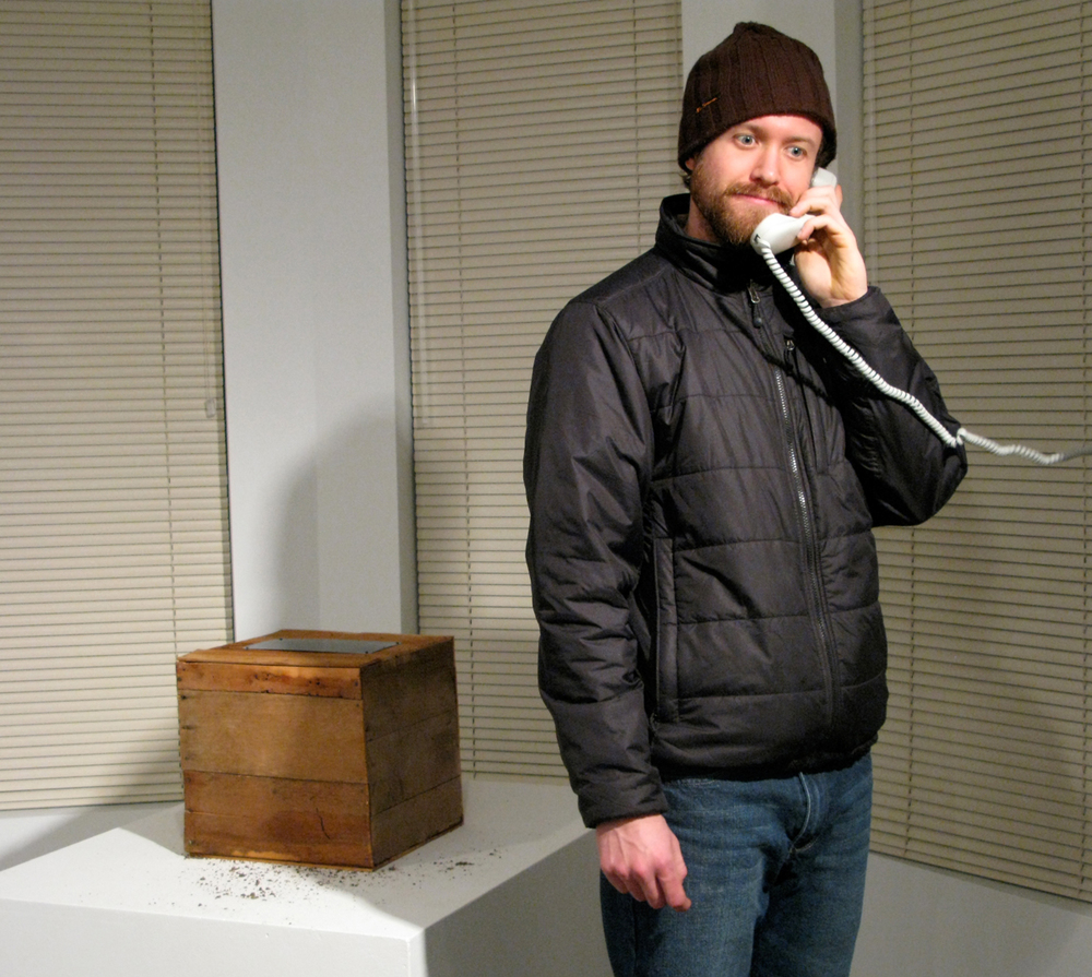 a man telephoning the time capsule to leave a message on the mobile phone inside