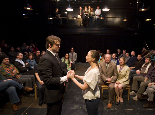 George and Emily are married in the 2009 production of Our Town. The folks sitting on the left andright are audience members, while those in the center facing the camera are cast members