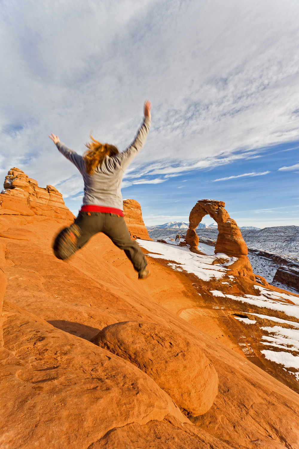 Hiker Leaping at Delicate Arch, Arches National Park, Utah