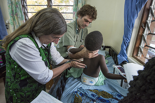 Dr. Terrie Taylor (left) and Dr. Karl Seydel (center) take a child's vitals in the pediatric malaria ward at Queen Elizabeth Hospital in Blantyre, Malawi, Africa.