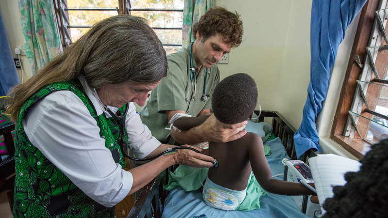 Dr. Terrie Taylor, left, and Dr. Karl Seydel take a child's vitals in the malaria ward at Queen Elizabeth Hospital in Blantyre, Malawi. Courtesy of Jim Peck/Michigan State University
