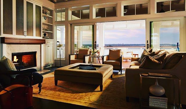 """Skyeblu"" living room, sunset glamour shot. ""Cocktails anyone?"". Click on link in the bio to see article about this house in Home Decor and Design Magazine. #luxuryliving #sunset #wrightsvillebeachnc #luxurylifestyle #luxuryhomes #waterfronthomes #wilmingtonarchitect #peridotinteriors #parkerconstructiongroup #mb_productions_nc #homedesigndecormagazine"