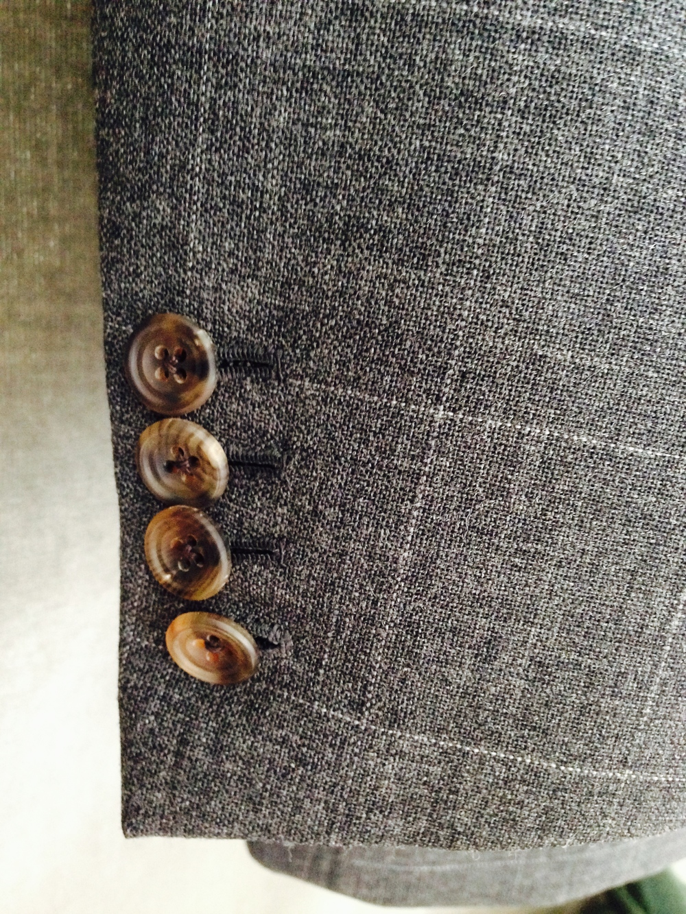 The cream and bone tones in these horn buttons bring out the lighter elements of the cloth, including the faint overcheck.