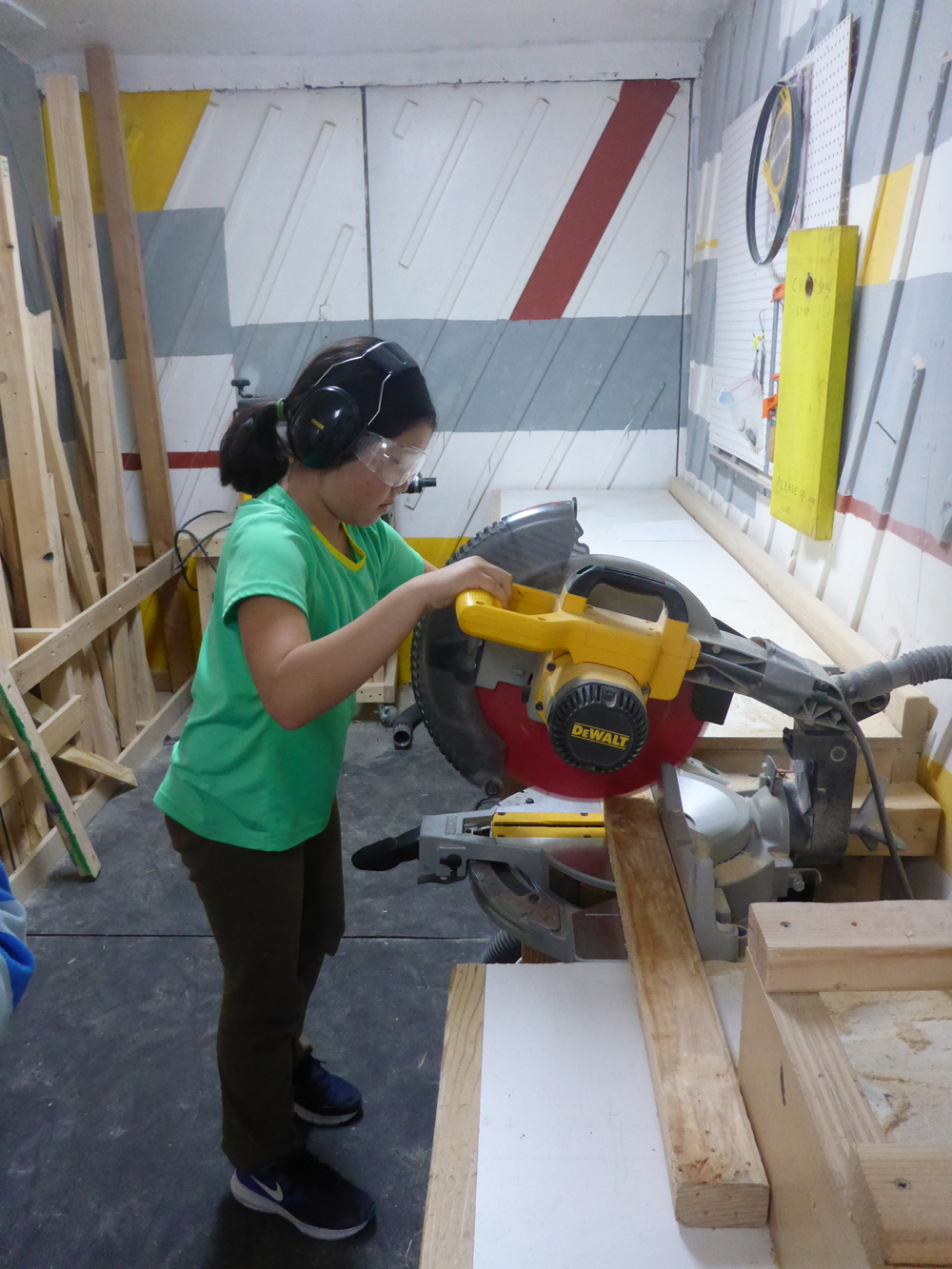 Ava makes a cut on the chopsaw!