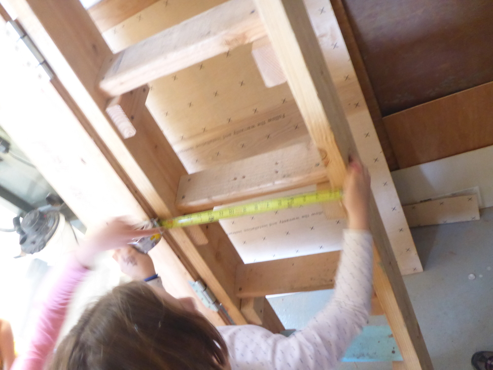 Using what works. Miel spots an existing ladder in the shop and decides to use it to help guide her measurements to determine rung length.
