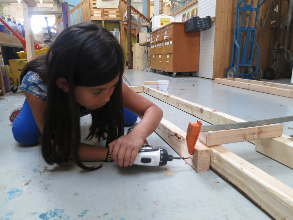 Maite grabs a drill and gets to work helping attach all the vertical ramp legs using the system established last week of driving only a single screw so they can be rotated upwards before being secured into place.