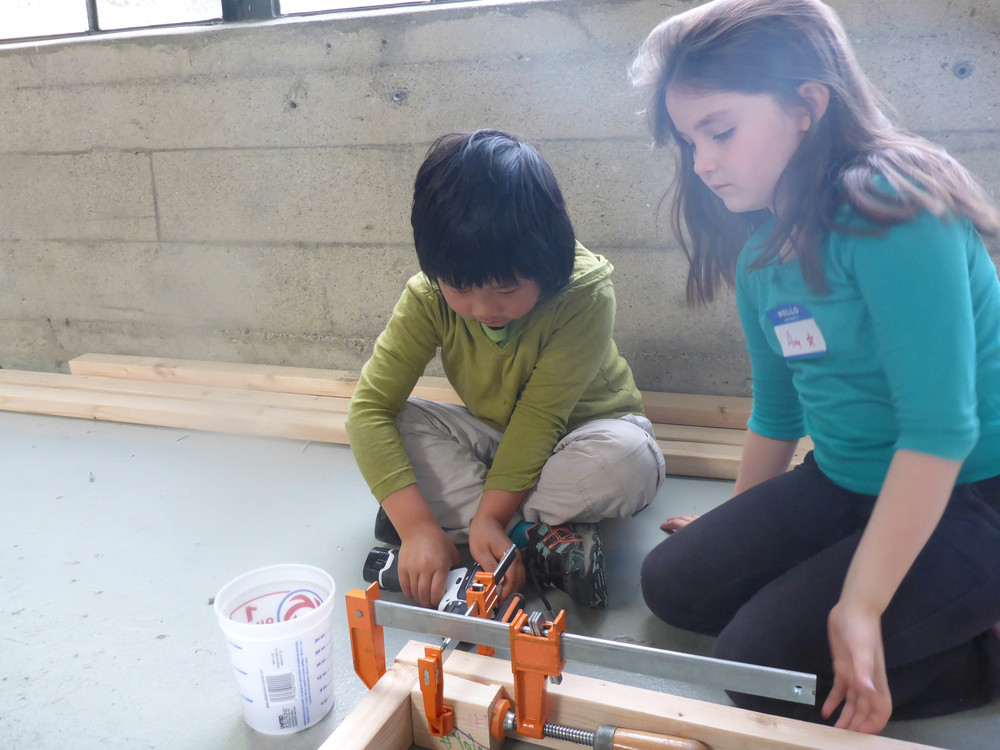 Orin and Ava take turns drilling pilot holes and driving screws to make a Barn wall.