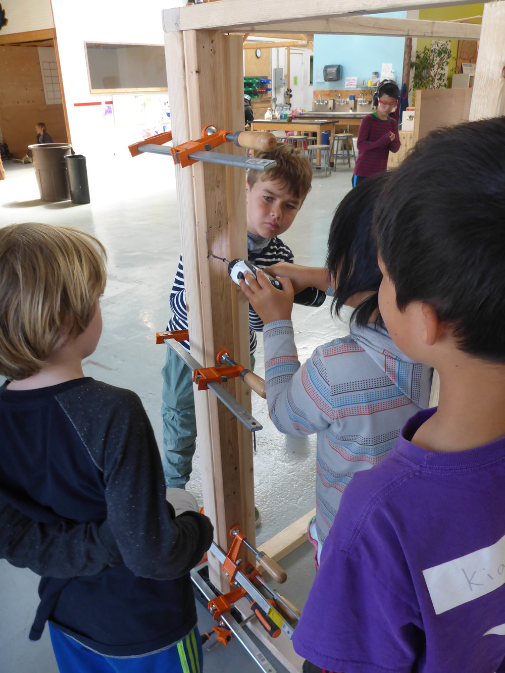 Ari, Oliver and Kian stand by after clamping to wall together, while Orin does some fastening.