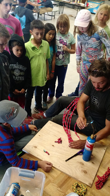 Josh teaches the kids how to cut rope with a hot knife, sealing the end so it doesn't fray.