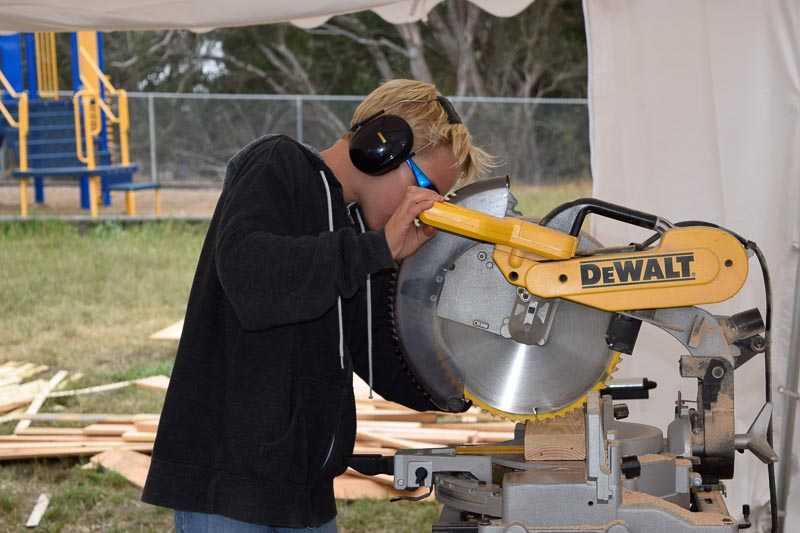 Ryker cuts wood on the chop saw for his team, the Kablooi