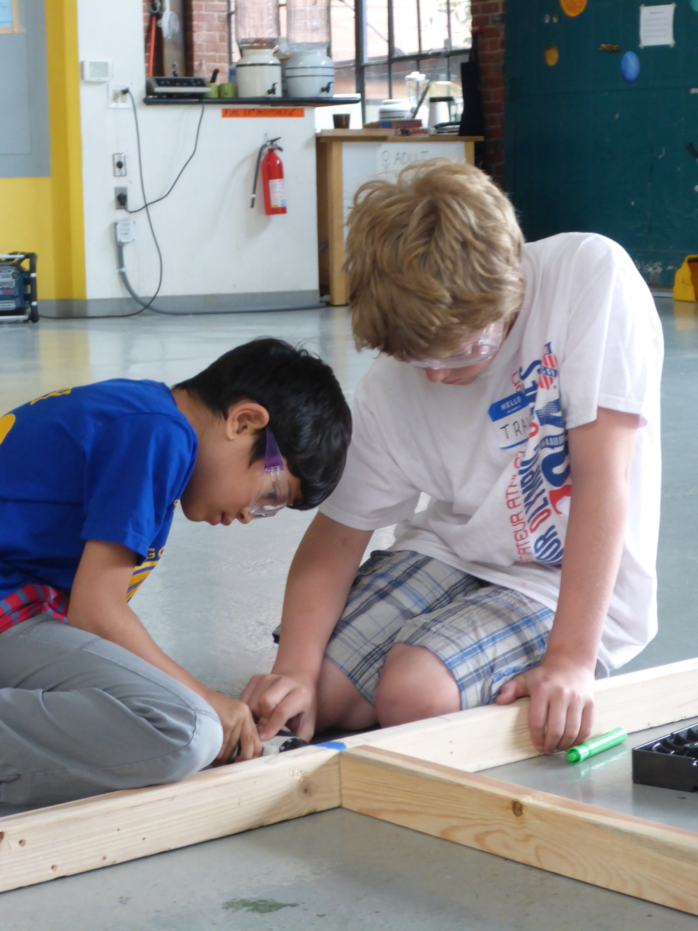 Travis and Atish help frame an Upside-Down wall.