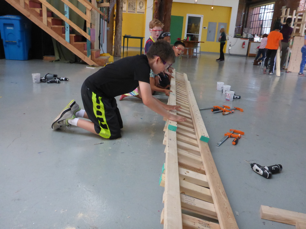 Jake, Brandon and Eli flip over a section of the bridge in order to connect shorter sections into one long bridge.