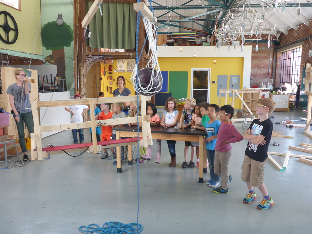 Eli, Toby, Zoe, Siri, Benjamin, Maddie, Sydney, Maya, Calder, Abe and Alex look on and offer suggestions for improvements to the swamp swing thing-a-ma-jig during the first full-fledged test of the mobile!