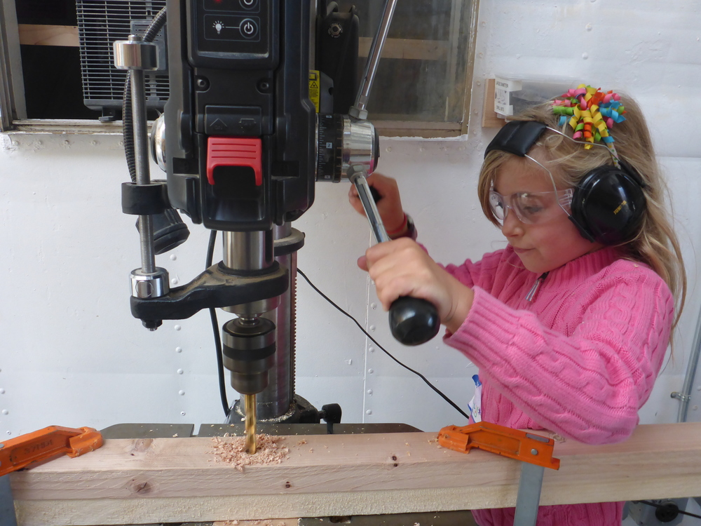 Maya uses the drill press to drill super straight holes where the main beam for the swamp swing will hang from the block and tackle.