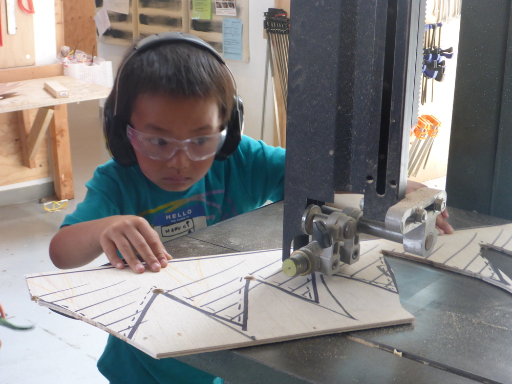 Haruki uses the bandsaw to cut out spikes for the alligator's back.