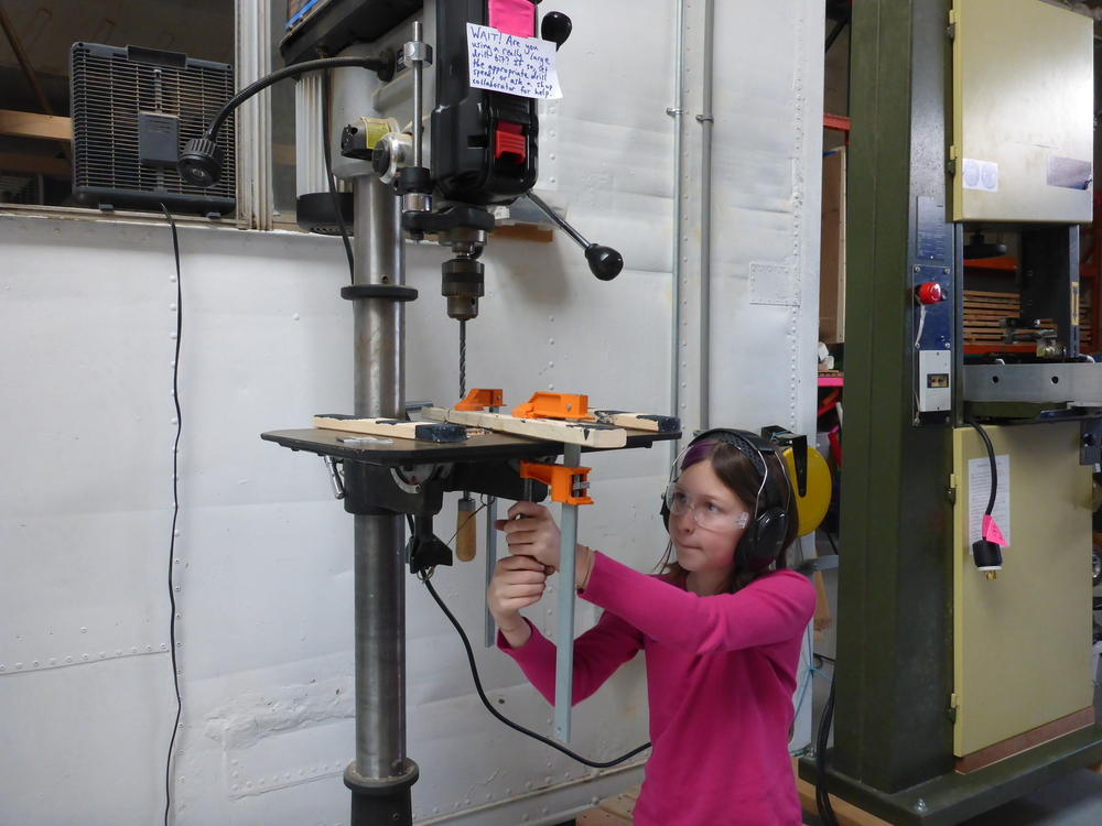 Lily's design for a chandelier involved drilling holes so that the 'gems' hanging from her chandelier could be attached with cord and dangle nicely. She learned how to change the speed on the drill press too!