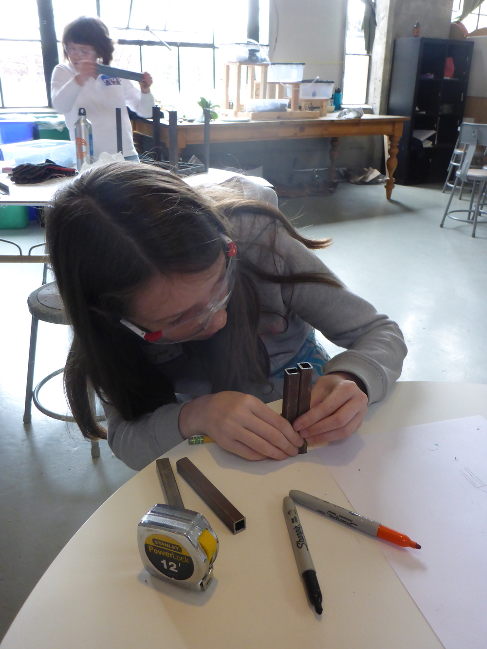 "Sophie measures some pieces of 1/2"" square tube to see if they will work for her table."