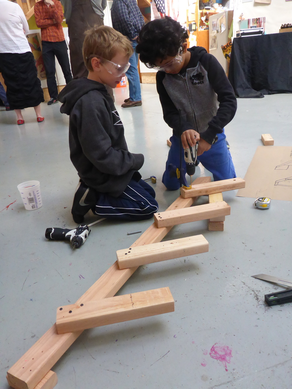 Gautam and Zach clamp and attach pieces of the stairs they are making.