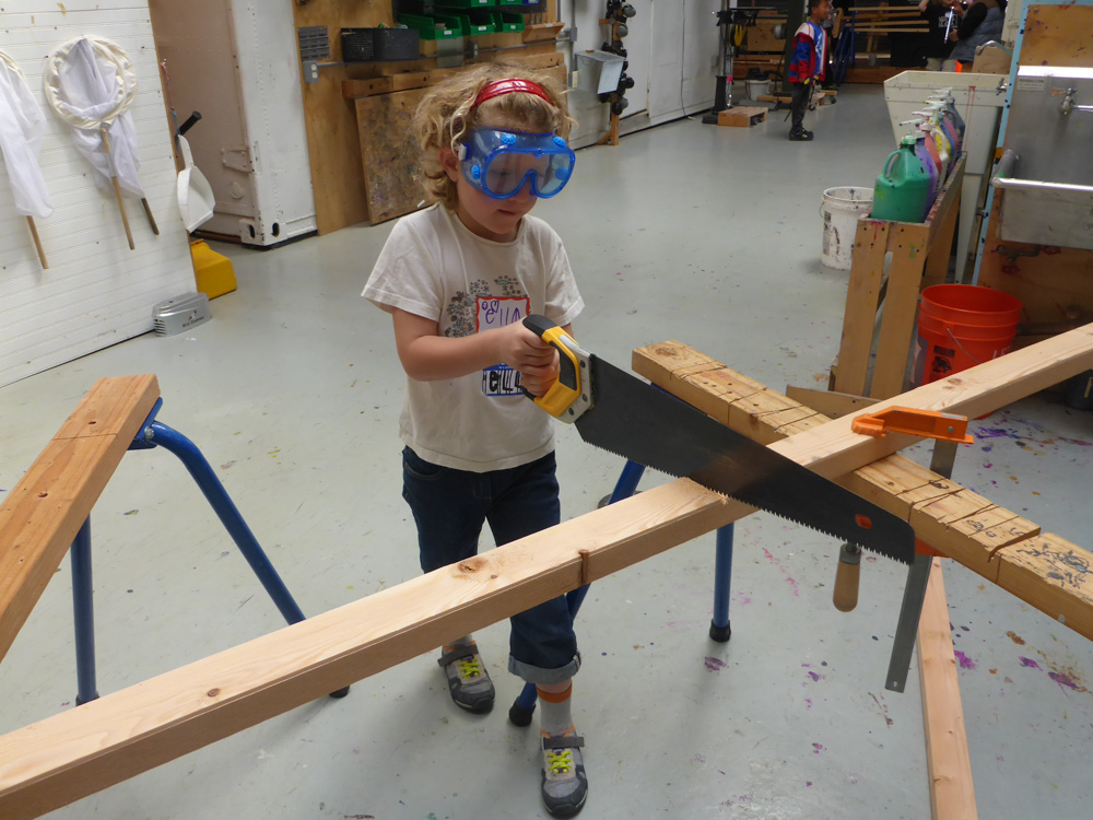Ella uses a hand saw to cut a specialty piece.