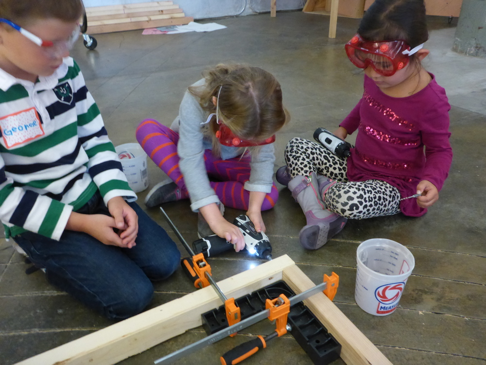 George and Charlotte and Lucia work as a team to drive some screws.