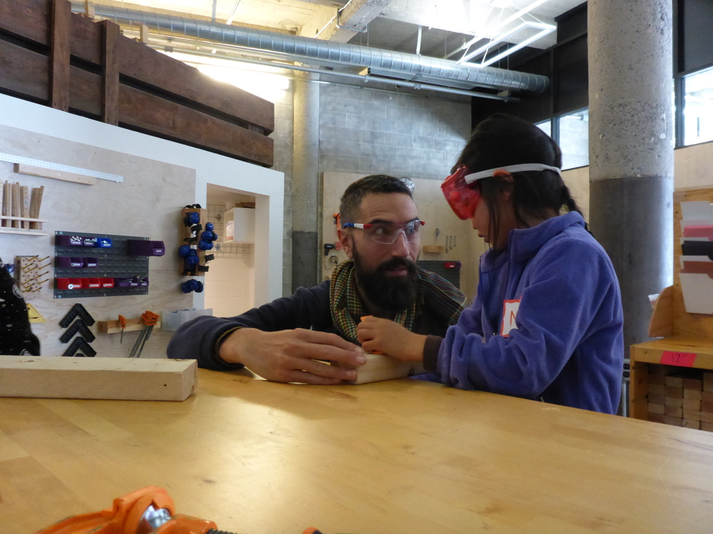 Nathan and Nova practice clamping a piece of wood to the table during tool practice.