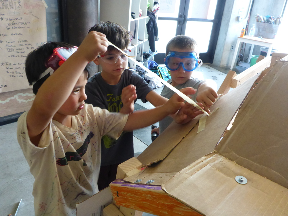More teamwork! Jonas and Aaron and August repair some cardboard connections in the Space Probe's rocket.