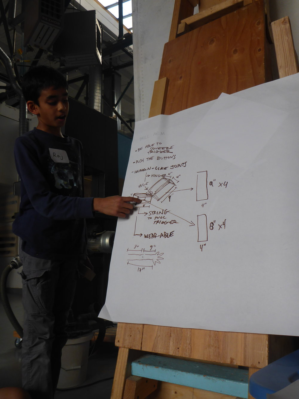 Raj explains the design trajectory for the drill arm team--a hinged sleeve that the drill can fit on the end of.