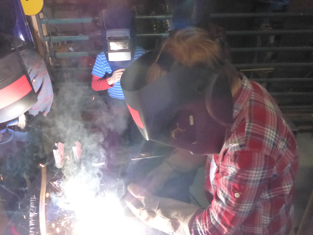 Sadie lays down her first bead! She noticed that at first the tip of the welding gun was too far away. This caused the electrode to get to long and break off!