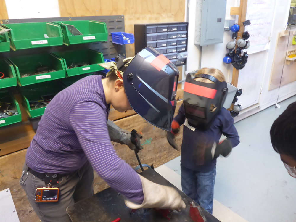 Amanda and Alex get ready to weld pieces for his tank.