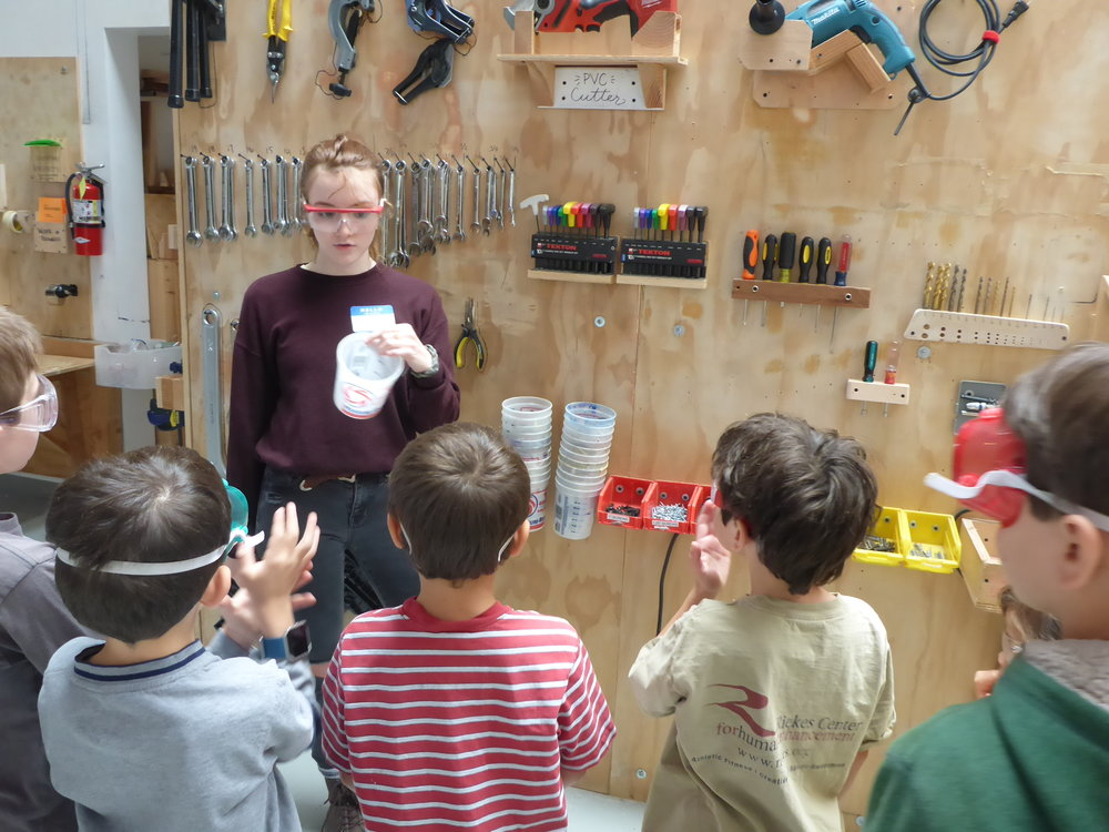 Frannie instructs a group of Tinkerers in the safe use of the drills, the location of the tools they will need, and how to keep pesky screws from rolling away (buckets!) while working on the floor of the warehouse.
