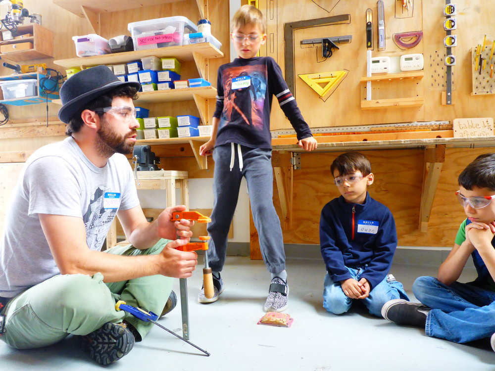During tool training, everyone learned about the different types of clamps we have in the Tinkering School shop. Brendon demonstrates to the group how to open and close our orange bar clamps (twisty clamps!).