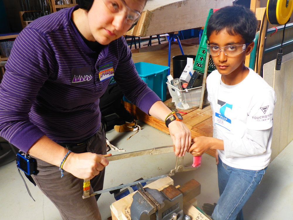 When the going gets tough, the tough get a hacksaw. Amanda teaches Ayush how to start a cut on using a hacksaw. His pieces was too small to use the plug-in tool to cut it, so these finishing details had to be done by hand.