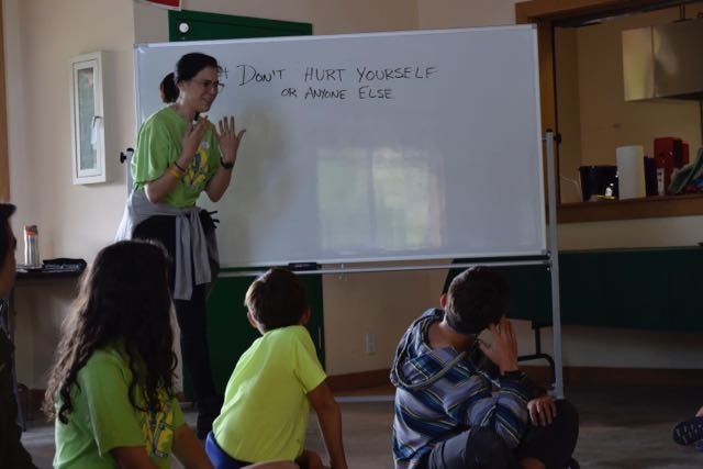 "Caroline, the Tinkering School Captain, discusses Rule #1 with the campers. Rule #2 is ""If you see a piece of fruit, and you want it, you must eat it,"" and Rule #3 is ""All disagreements are settled with Roshambo."" This group decided by majority that we throw on the ""Bo!"""