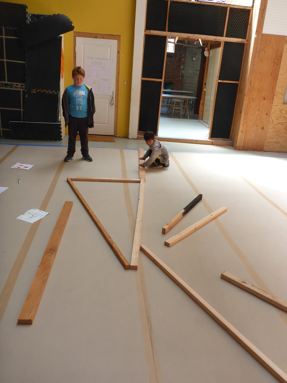 Over on the head team, Bennett and Owen laid out their pieces of wood on the floor so they could get an idea of the scale and shape of their part of the insect.