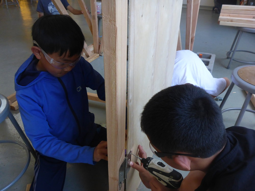 Joey helps from inside the abdomen while Ben mounts a hinge for the door into the bug's belly.