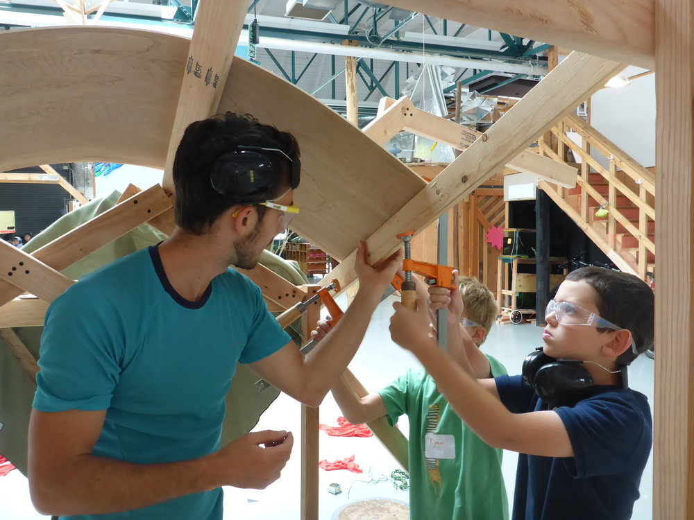 Evan holds the plywood exoskeleton in place while Mo tightens the clamp.