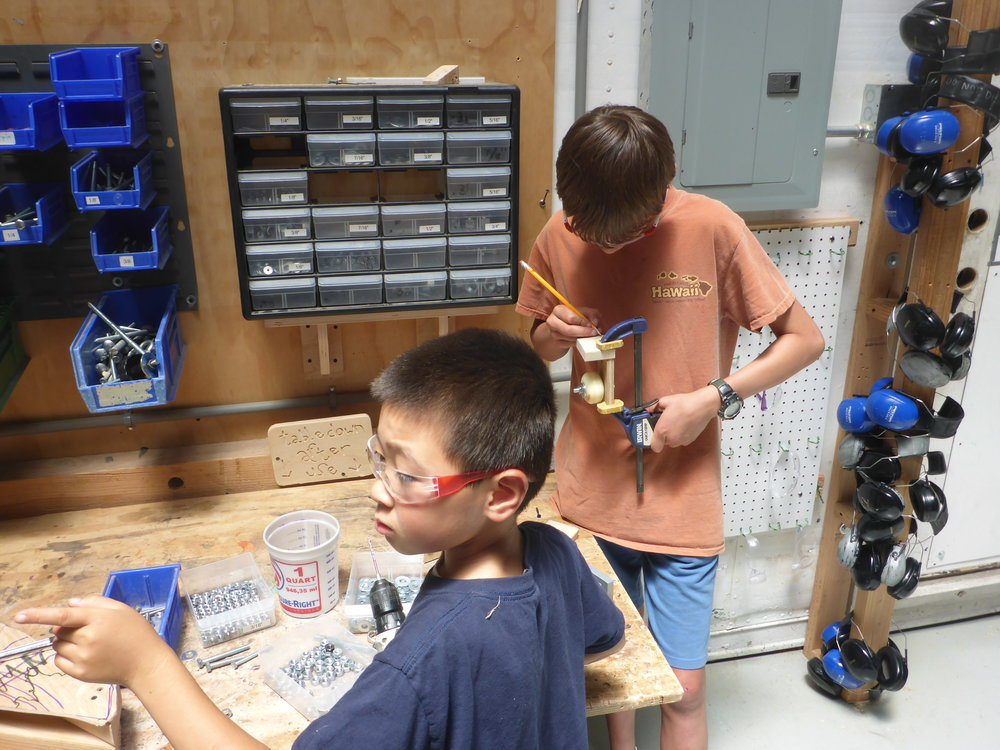 Then, they set-up on a table in the shop, cutting little pieces of wood, drilling holes and tinkering with different combinations of bolts, washers, nuts and bracket designs.