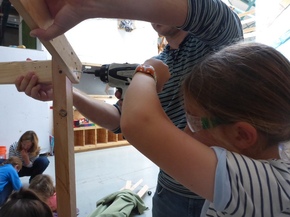 Trixie takes some screws out of the frame of the thorax, while a parent holds the wood in place.