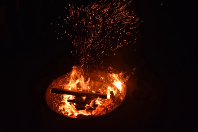We pass around the sawdust collected from the chop saw and take turns throwing handfuls of it into the flames. Oooh. Aaah.