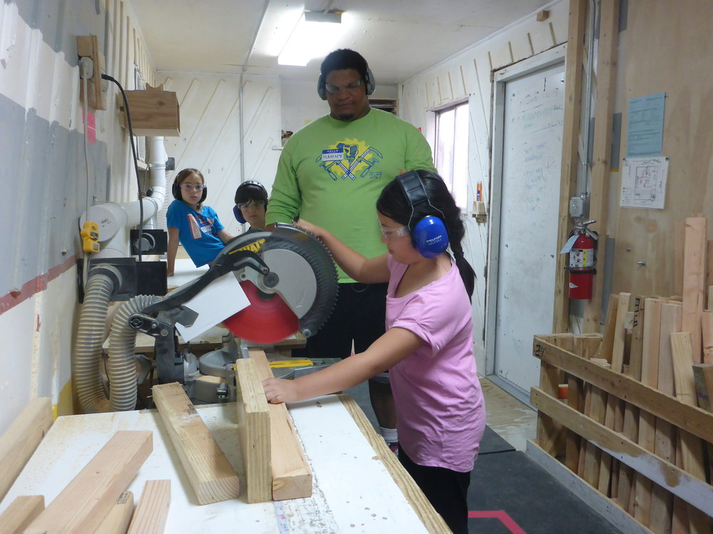 Manny steps aside while Mia makes her first cut on the chopsaw. Great form!