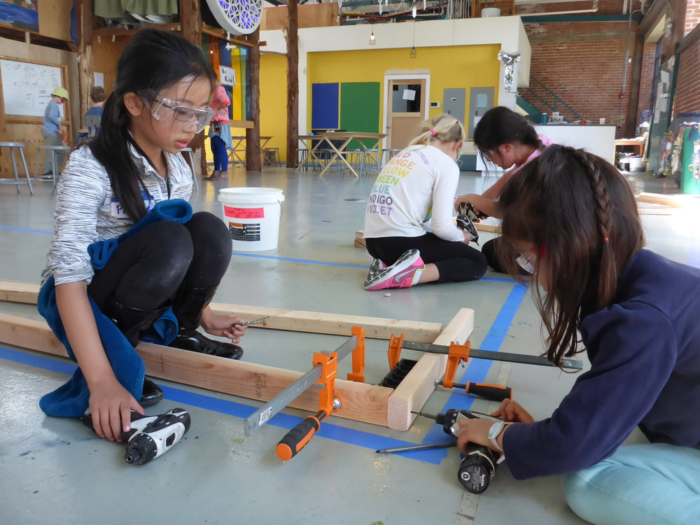 Phoebe and Minyoung work on constructing a frame for the base of the coral reef. The reef builders started by laying out the size of a few sections of coral on the floor, then started putting pieces together.