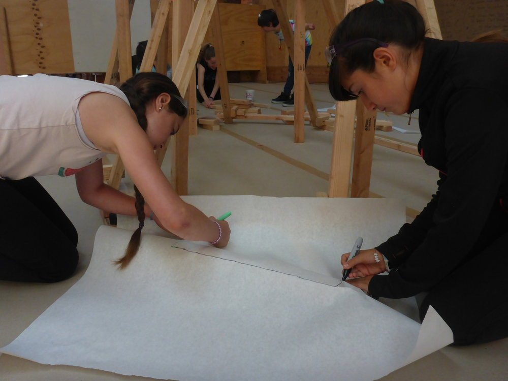 Justine and Julia carefully trace one of their flippers before transferring the shape onto a sheet of thin plywood.