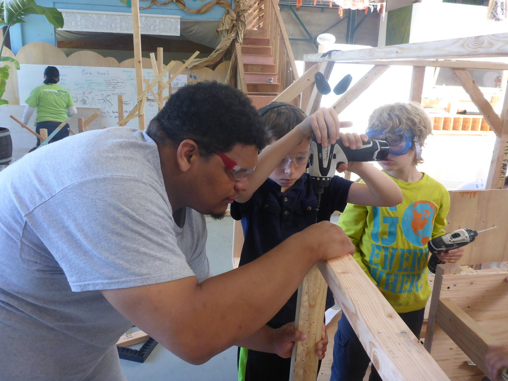 Manny human clamps a few pieces of wood together so that Santi and Jacob can drill holes and drive in screws. Since this side of the submarine is supposed have a door, these sections of wall were hanging out in space, making them pretty tricky to work on.