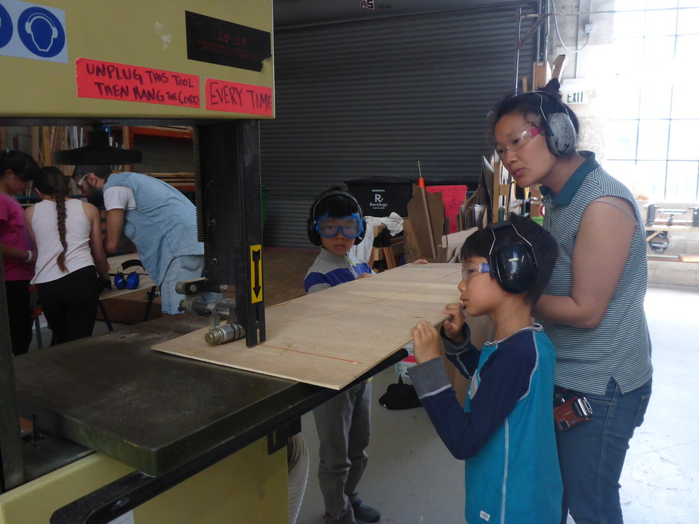 Minjae, Nikki and Varit carefully cut plywood for the seat of the second bench. Building number 2 of a thing always goes so much faster than building number 1!