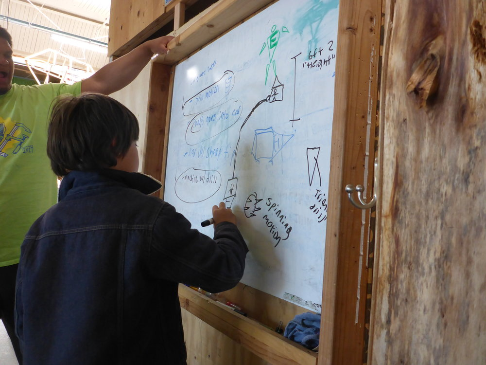 Jack draws a design idea for the boring machine on the group's whiteboard. This team had so many different ideas for how to build this tunnel digging machine! At times, we needed to remember what we want our machine to be able to do--dig a tunnel through the ground--and make compromises in order to be able to realize this design goal.
